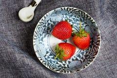 Fragola fresca in ciotola ceramica sul panno grigio del piatto immagini stock libere da diritti