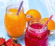 Fragola fresca e cocktailes arancio con i frutti Immagini Stock