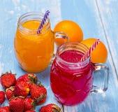 Fragola fresca e cocktailes arancio con i frutti su una r di legno Fotografie Stock