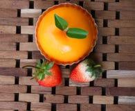 Fragola fresca e dolce arancio sulla stuoia di legno Fotografia Stock