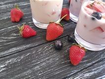 Fragola, muesli della farina d'avena del rinfresco del frullato del dessert del yogurt di mirtillo su un fondo di legno nero Fotografie Stock