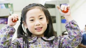 Fragola sveglia asiatica divertente sorridente della frutta di condizione e della tenuta della ragazza Fotografie Stock Libere da Diritti