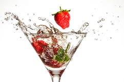Fragole che cadono in vetro di Martini Immagine Stock
