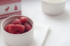 Fragole congelate in un piatto bianco su una tovaglia bianca vicino alla scatola di Natale Fotografia Stock