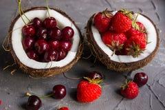 Fragole e ciliege a metà della noce di cocco Fotografia Stock