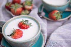 Fragole e tazza fresche di latte su una tovaglia immagini stock