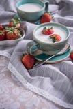 Fragole e tazza fresche di latte su una tovaglia fotografia stock libera da diritti
