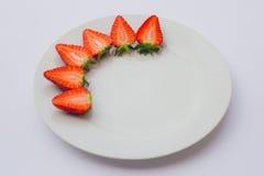 Fragole organiche fresche divise in due e decorate su un piatto bianco Fotografie Stock