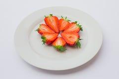 Fragole organiche fresche divise in due e sistemate sul piatto bianco Fotografia Stock
