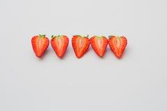 Fragole organiche fresche divise in due e sistemate in una linea su un fondo bianco Immagine Stock