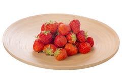 Fragole su un piatto di legno isolato su bianco Fotografia Stock