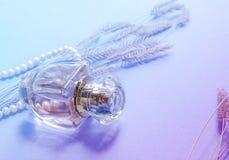 Fragrância da mulher em uma garrafa de vidro em um fundo azul, um presente para uma menina Imagens de Stock