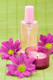 Fragrance bottle. With flowers and candle on green bamboo Royalty Free Stock Image