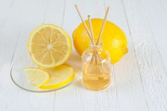Fragrance Lemon sticks or Scent diffuser. Fragrance sticks or bottle Scent diffuser with Lemon on wooden background royalty free stock photo