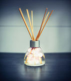 Fragrance room diffuser with bokeh and sticks on dark table Royalty Free Stock Images