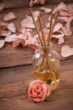 Fragrance sticks or Scent diffuser. With rose flowers on wooden background royalty free stock photo