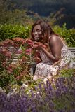 The fragrance of the summer. Young curvy woman in a summer dress enjoys the fragrance of flowers stock image