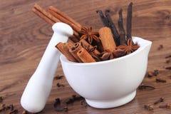 Fragrant anise, cinnamon and vanilla sticks in mortar on rustic board Stock Photo