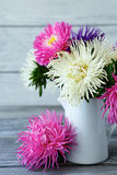 Fragrant asters in a jug on the boards Royalty Free Stock Image