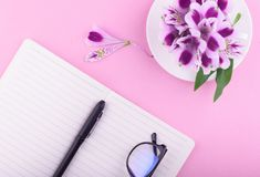 Fragrant beautiful flowers, a pink background, a notebook with a pen and glasses. View from above. Fragrant tea in a white cup, beautiful flowers, a pink stock photos