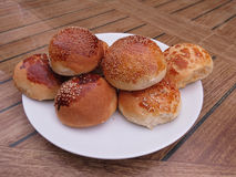 Fragrant bun on a plate. On a white plate neatly laid out round buns with sesame and poppy seeds Stock Photos