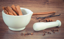 Fragrant cinnamon sticks in mortar and spices on rustic board Stock Photos