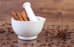 Fragrant cinnamon sticks in mortar and spices on rustic board Stock Photo