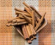 Fragrant cinnamon sticks. Oriental fragrant cinnamon sticks in wooden bowl royalty free stock photos