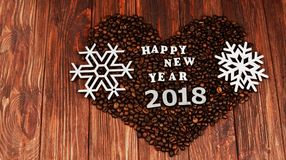 Fragrant coffee beans in the form of a heart. With the inscription Happy New Year 2018 and snowflakes on a wooden background Stock Images