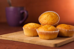 Fragrant cupcakes lie on a wooden table.  Stock Images