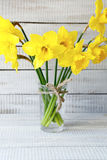 Fragrant daffodils in a vase on wooden boards Royalty Free Stock Photo