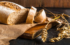 Fragrant fresh-baked rye bread. On a black wooden table. Spikelets of wheat and rye close. Rustic Style Royalty Free Stock Image