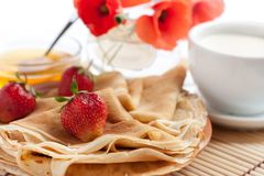 Fragrant golden pancakes and fresh milk. Honey and red poppies Royalty Free Stock Photo