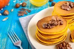Fragrant golden pumpkin pancakes with honey and walnuts on a blue wooden background. Stock Images