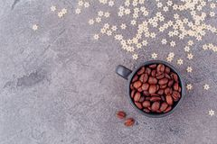 Fragrant grains of black coffee in a black glass on a gray concrete background stock photos
