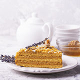 Fragrant homemade honey cake  with nuts and  lavender on gray concrete background    fresh  in the horizontal version Royalty Free Stock Photo