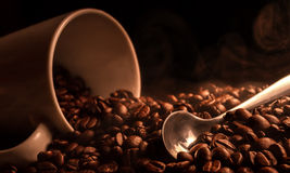 Fragrant hot coffee. Spoon and a smoking mug of coffee beans Stock Photography