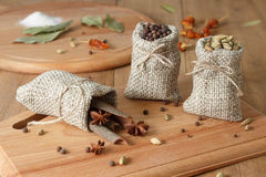 Fragrant pepper, cardamom and Cinnamon sticks with stars anis  in the linen sacks on the wooden board at rustic stile.Salt, leaves Royalty Free Stock Images
