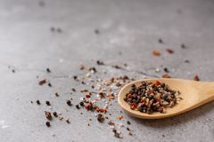Fragrant pepper peas in a wooden spoon on a concrete background stock image