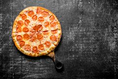 Fragrant pepperoni pizza on the cutting Board. On dark rustic background royalty free stock photos