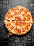 Fragrant pepperoni pizza on the cutting Board. On dark rustic background royalty free stock photo