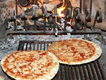 Fragrant pizza baked in a wood fireplace with a wood-burning ove Stock Photo