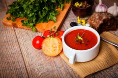 A fragrant red borscht in a white plate with a lots of vegetables on wooden background. Food concept. Royalty Free Stock Photography