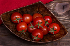 Fragrant red cherry tomatoes on a branch on the old retro board Stock Photo