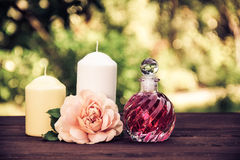 Fragrant rose oil in a beautiful glass bottle. Pink elixir, candles and flowers. Spa concept. Vintage tinting. Fragrant rose oil in a beautiful glass bottle royalty free stock photo