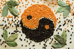 Fragrant spices and beans in the form of a yin yang sign. Black fragrant round pepper with orange lentils on a light background form a Buddhist sign yin yang stock photo
