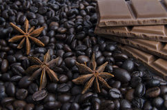 Fragrant spices, coffee and chocolate. Background of black coffee decorated with chocolate and spices Stock Photos