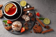 Fragrant tea in a black cup on a black plate with biscuits, lemon, cinnamon and fruits royalty free stock photos