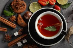 Fragrant tea in a black cup on a black plate with biscuits, lemon, cinnamon and fruits. Cookies strawberries lime ieta sugar fresh food dark glass healthy stock photography