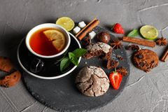 Fragrant tea in a black cup on a black plate with biscuits, lemon, cinnamon and fruits. Cookies strawberries lime ieta sugar fresh food dark glass healthy royalty free stock image